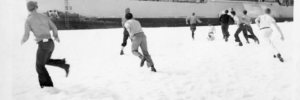 People running and playing in snow, watched from a ship
